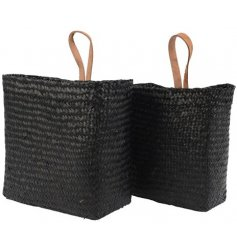 A set of 2 chic and stylish woven sea grass baskets. Each has a real leather handle in tan.