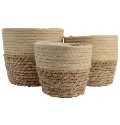 A set of 3 two-tone woven baskets in beige and brown colours. Each is fully lined with plastic.