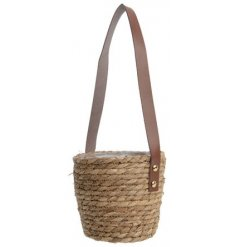 A stylish woven hanging basket with plastic lining and a tan leather handle.