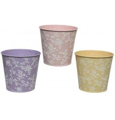 An assortment of 3 water resistant iron planters in pretty pastel colours. Each has a delicate floral design.