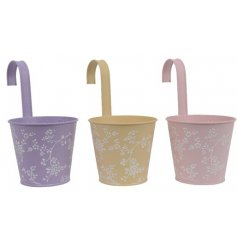 An assortment of 3 pretty pastel coloured planters with hook to hang. Each has a matt finish and floral design.