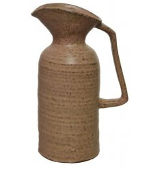 A rustic stoneware jug with square handle and curved spout