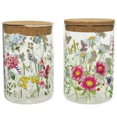 An assortment of 2 glass storage jars with cork lids. Each is decorated with a bright and beautiful floral decal.