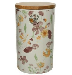 this tall porcelain storage jar is covered with a delicate floral design and topped with a wooden lid