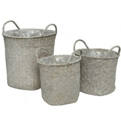 A set of 3 white washed woven baskets with handles and a plastic lining. Handmade with a rustic feel.