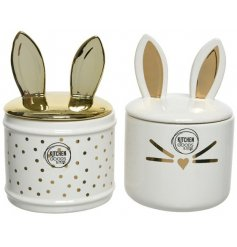 An assortment of 2 gold and cream dolomite storage jars with bunny ears.