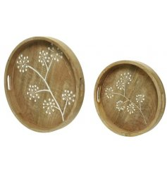 A set of 2 pretty mango wood trays with a white flower detail. Each round tray has a unique wood grain