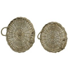 A set of 2 rustic rattan trays with handles. A chic round design with woven, natural pattern.