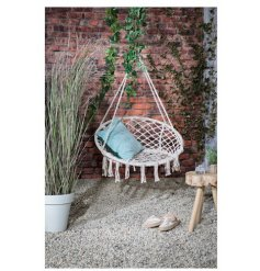 A bohemian hammock swing chair in natural. Complete with fringing.