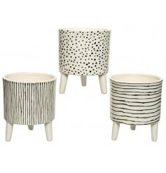 A mix of 3 stylish planters with feet. Each has a contemporary monochrome design with a hand drawn aesthetic