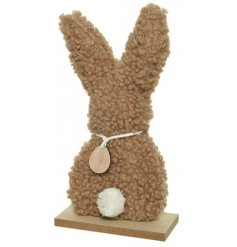 An adorable bunny rabbit decoration with brown teddy fabric. Complete with a fluffy tail and wooden egg.
