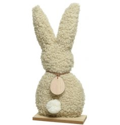 A cream teddy fabric bunny decoration with a fluffy tail and wooden egg decoration.