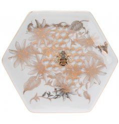 A stylish hexagon shaped ceramic trinket dish with an added luxe golden beehive inspired decal