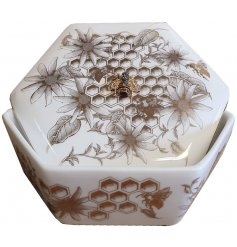 A stylish hexagon shaped ceramic trinket box and lid with an added luxe golden beehive inspired decal