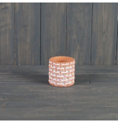 A small sized round terracotta pot decorated with a weave inspired decal and set with a white washed tone