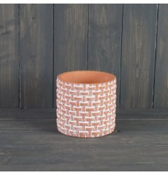 A large sized terracotta pot set with a white washed tone and added woven inspired pattern