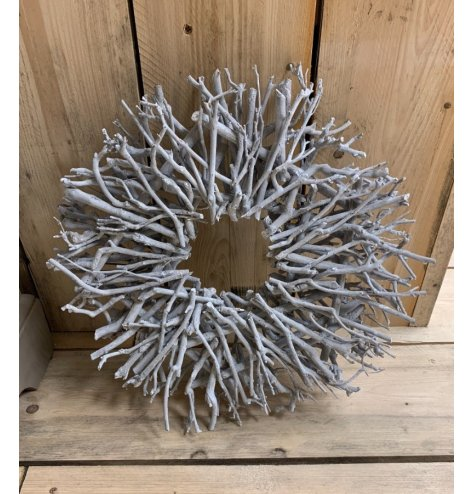 A large natural twig wreath set in a circular display, complete with a powered white finish