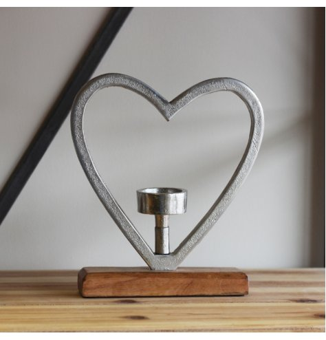 A chunky aluminium heart outline stood on a wooden base with a T-light centred inside.