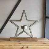 A chunky aluminium star outline stood on a wooden base with a T-light centred inside.