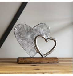 A simple and rustic-inspired wooden decoration with an added aluminium double heart display on it