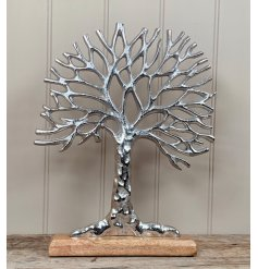 a silver toned aluminium tree of life ornament on a block wooden base