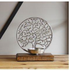 A beautiful aluminium tree of life ornament set upon a wooden block base