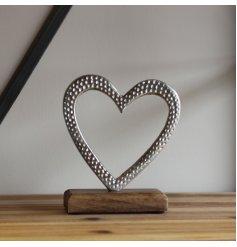 A small aluminium heart ornament placed atop a natural wooden block
