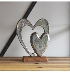 An ornamental aluminium double heart ornament set on a natural wooden block base