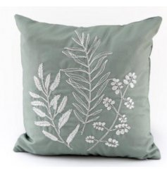 A soft to the touch and plump looking cushion featuring a charming mellow green hue and pretty embroided floral design