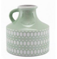 A charming and sleek looking porcelain vase set with a sage green base tone and embossed circular design