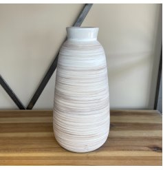 A tall standing ribbed vase with a neutral colour tone and a rustic finish
