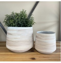 An assorted sized set of round ribbed vases with neutral colour tones and a rustic finish