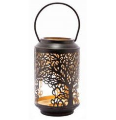 A beautifully detailed metal lantern, featuring a cut out tree decal and added block gold inner tone