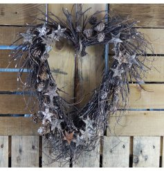 A beautifully decorated twig wreath with a charming heart shape