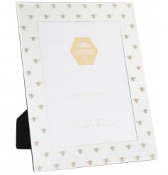 A beautiful mirrored photoframe with small golden bee decals and a glitter finish