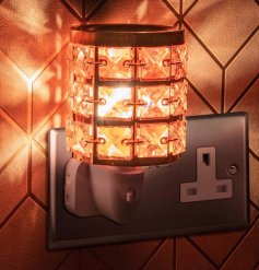 A plug in operated desire aroma light decorated with glitzy orange crystals and a rosegold edging