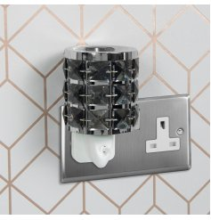 A plug in operated desire aroma light decorated with glitzy black crystals and a silver tone edging