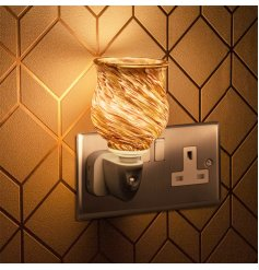 A plug in powered Desire Aroma Dispenser with a stunning swirling sands decal and warming glow