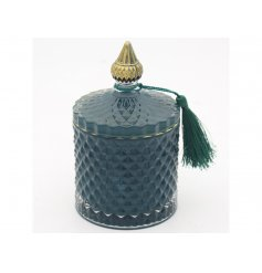A sleek green toned diamond ridge candle holder complete with gold accents and a fuzzy tassel