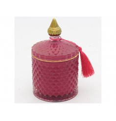 A sleek red toned diamond ridge candle holder complete with gold accents and a fuzzy tassel