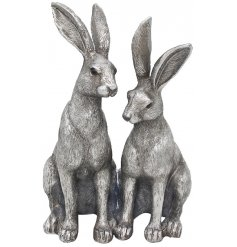 A set of twin posed ornamental hares decorated with realistic features and set with a rustic silvered tone