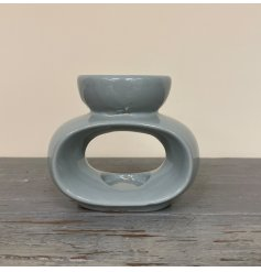 A small ceramic oval shaped tlight holder with an added wax and oil dip dish