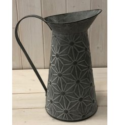 a distressed metal jug with a trendy geometric embossed decal