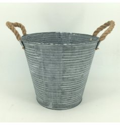 An overly distressed round zinc planter set with a ribbed edging, white wash finish and chunky rope handles for decal