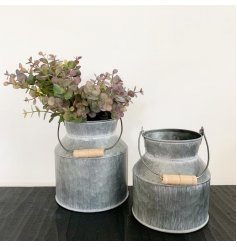 a small decorative metal churn with an overly distressed setting and wooden handle to finish