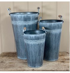 a tall decorative metal vase with an overly distressed setting and chunky rope handle to finish
