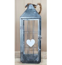 a tall standing metal lantern with a white washed finish and chunky rope handle