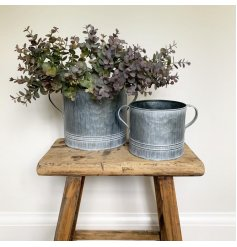 a small decorative metal pot with an overly distressed setting and tapered ear handles