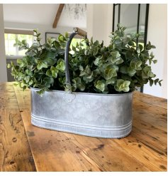 Set with an overly distressed coating, a large decorative zinc trug with an added metal and wood handle