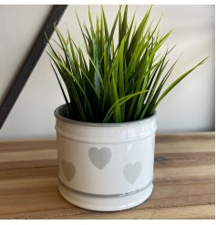 A chic and simple round pot featuring a grey ridged decal and faded heart print surround